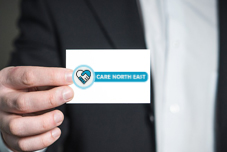 Image of a businesman holding Care North East Contact Card